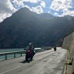 Two riders along the coastline road of Lake Livigno