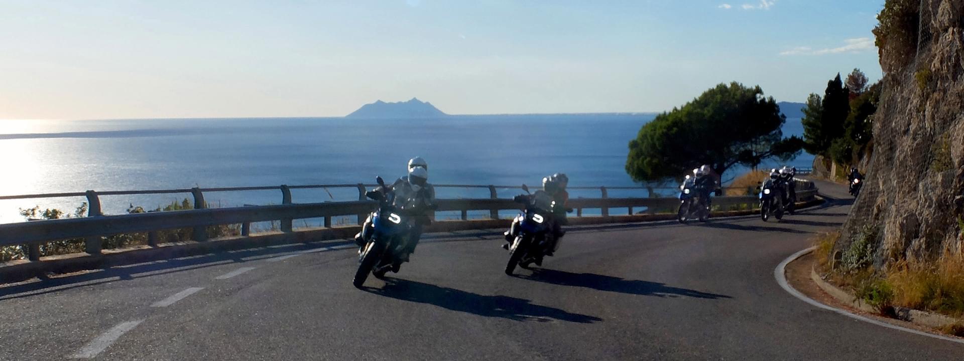 BMW riders along a beautiful Italian coastline road